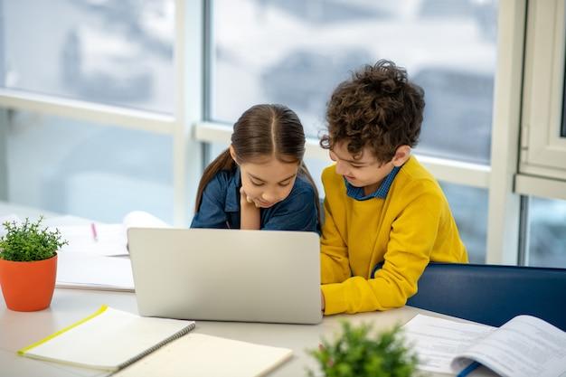 노트북을 사용하여 작업을 수행하는 소녀를 돕는 소년
