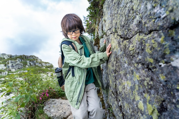여름에 산에서 하이킹 하는 소년. 등반과 바위에 기대어 아이입니다. 아이 들과 함께 여행 개념입니다.