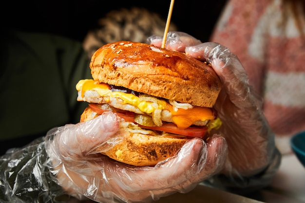 Мальчик держит в руках гамбургер и готовится его съесть