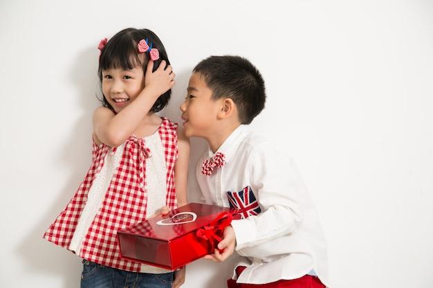 흰색 배경을 가진 소녀에게 선물을 주기 위해 선물을 들고 있는 소년.