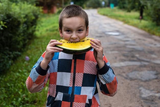 Мальчик держит желтый арбуз и хочет его съесть