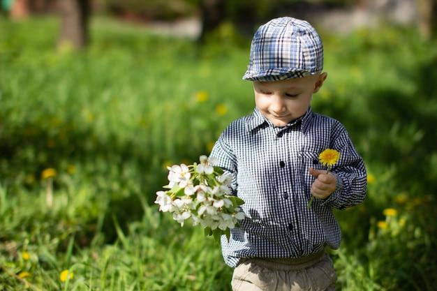 男の子が手に花を持っています