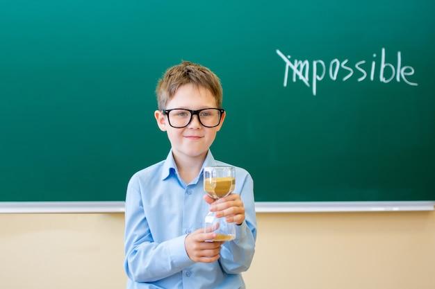 파란색 셔츠를 입은 소년이 칠판에 서서 손에 모래 시계를 들고 모든 것이 가능하다는 개념을 들고 있습니다.