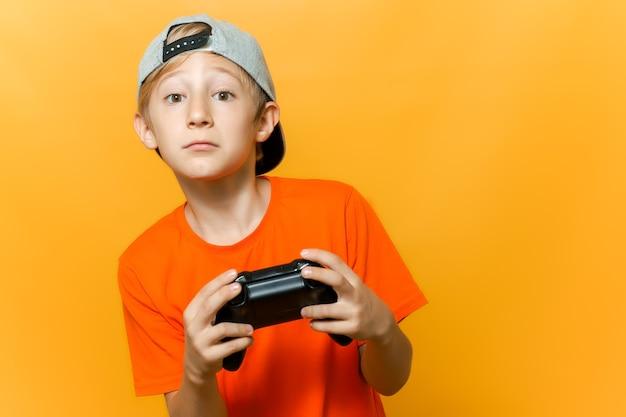 帽子とオレンジ色のtシャツを着た少年がゲームパッドを手に持ってコンピュータゲームをプレイしています