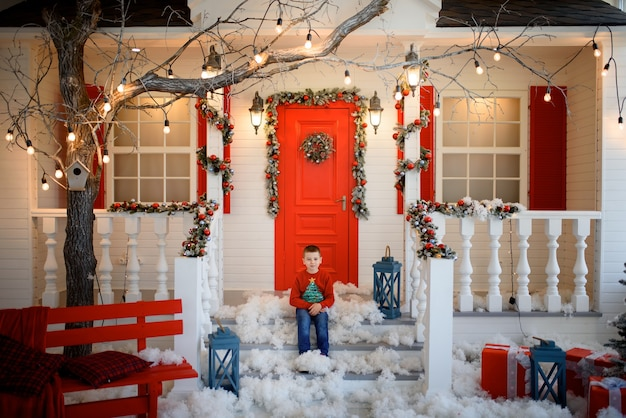 クリスマスのスウェットシャツを着た男の子が家の階段に座っています