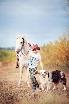 Мальчик в ковбойской шляпе идет по полю и ведет лошадь и пастушью собаку. жизнь на ферме, общение ребенка с животными