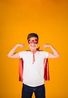 영웅 의상과 마스크를 쓴 소년은 텍스트를 위한 장소가 있는 노란색 배경에 힘을 보여줍니다
