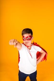 영웅 의상을 입은 소년이 문자를 위한 장소가 있는 노란색 배경을 돕기 위해 서둘러