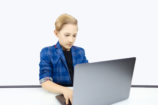 ジャケットを着た男の子がコンピューターで入力しています