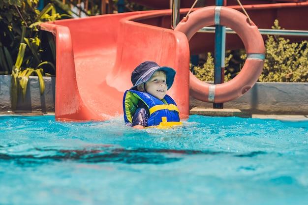 Мальчик в спасательном жилете соскальзывает с горки в аквапарке.