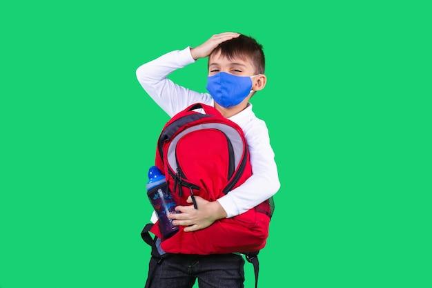 마스크를 쓴 소년이 붉은 색 가방을 들고 있다 물 한 병이 이마에 손을 대고 코로나바이러스 바이러스를 막습니다