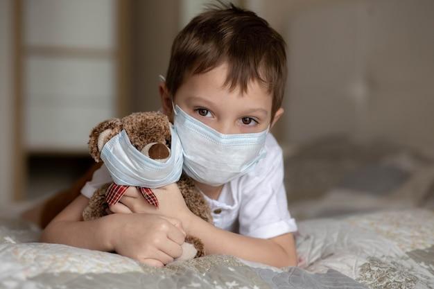 ベッドに横になり、マスクでテディベアを抱き締めるマスクの少年。セレクティブフォーカスの画像。高品質の写真