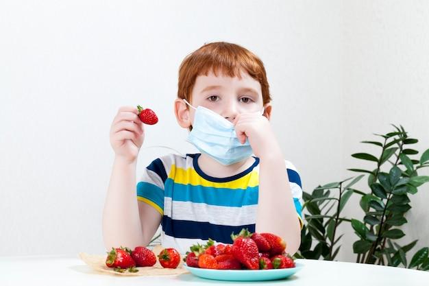 Мальчик в лечебной маске и спелой клубнике, маска мешает съесть десерт во время пандемии вирусов и болезней