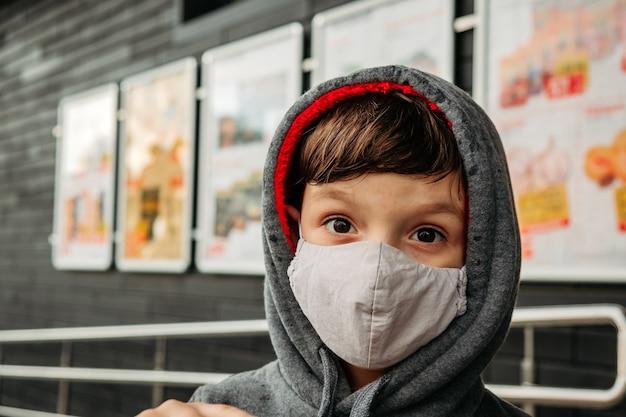 Мальчик в защитной маске заходит в супермаркет