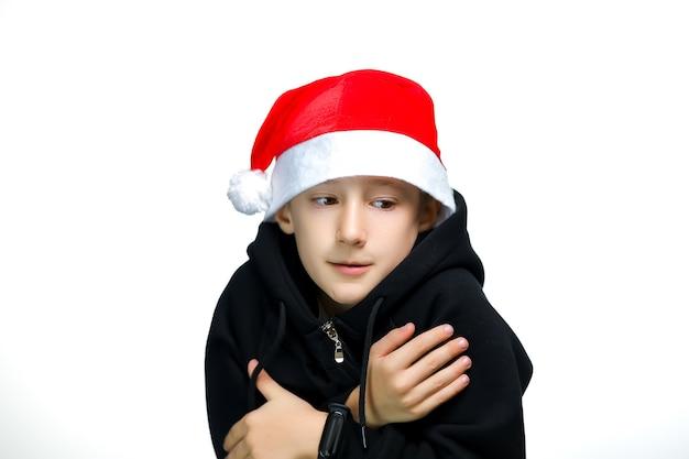 Мальчик в красной шапке санты бросился от холода, держась за плечи обеими руками