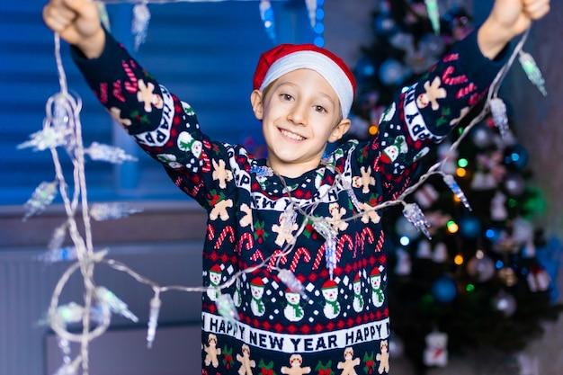 네온 조명 크리스마스 트리의 배경에 그의 손에 garlands와 산타 클로스 모자에 소년