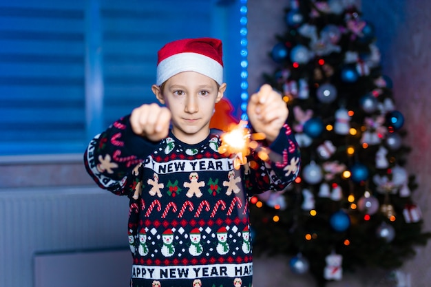 네온 lightin와 함께 크리스마스 트리의 배경에 그의 손에 폭죽과 산타 클로스 모자에 소년