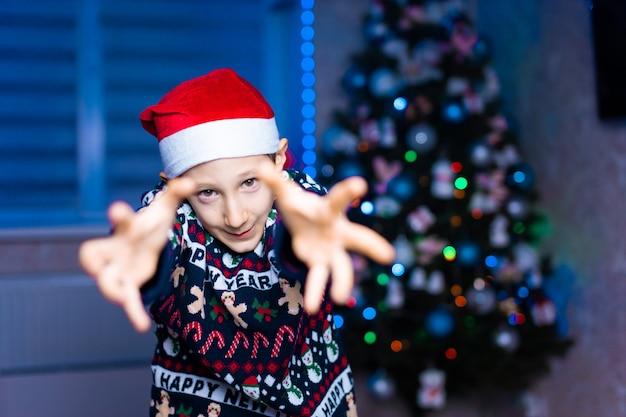 네온 조명 크리스마스 트리 배경에 산타 모자 소년