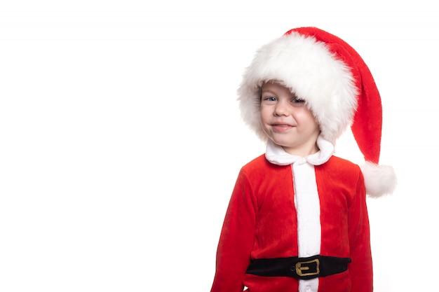 В кадр смотрит мальчик в костюме санты на белом фоне.