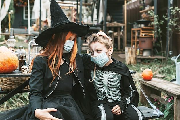 Мальчик в костюме скелета и девушка в костюме ведьмы в защитной маске на вечеринке в честь хэллоуина в новой реальности из-за пандемии covid