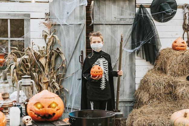 Covid 전염병으로 인해 새로운 현실에서 할로윈 파티에서 보호용 안면 마스크를 쓰고 해골 의상을 입은 소년