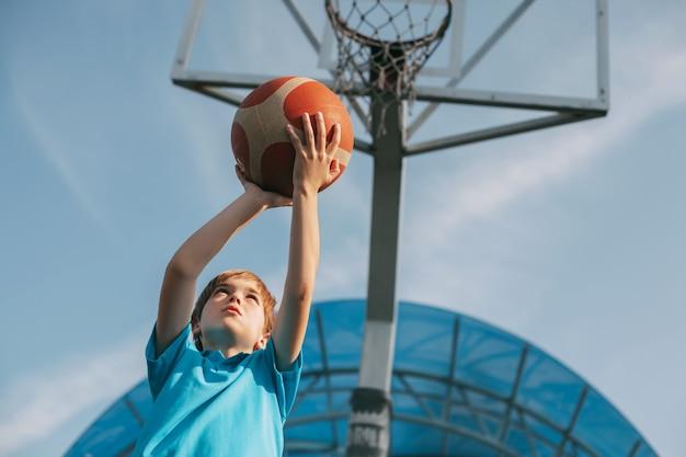 スポーツユニフォームを着た少年がバスケットボールのバスケットにボールを投げます。子供がバスケットボールをします。