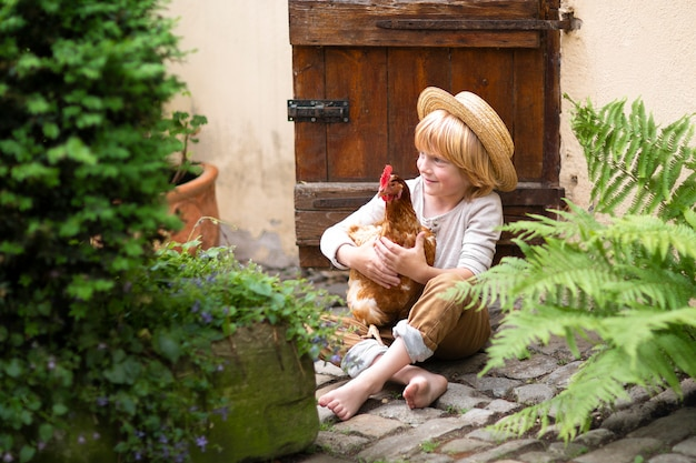 クローゼットへの小さな木製のドアの近くの石の道に座っている麦わら帽子の少年
