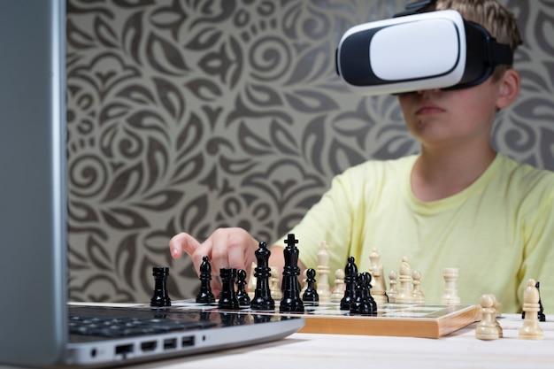 バーチャルリアリティヘッドセットの男の子がラップトップでチェスをします。情報技術を使用してチェスをすることを学ぶ