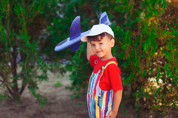 거리에 흰 모자를 쓴 소년이 글라이더 유아와 함께 놀아 그의 손에 비행기가있는 아이