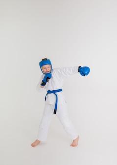 青いベルトの白い着物の男の子は、白い背景にパンチを作ります