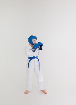 파란색 벨트가 달린 흰색 기모노를 입은 소년이 흰색 배경에 포즈 옆으로 서 있습니다.