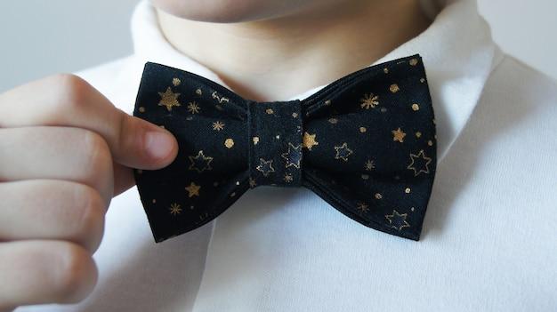 Мальчик в белой рубашке поправляет элегантный черный галстук-бабочку.