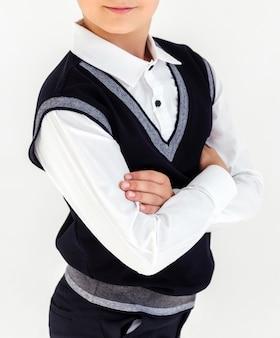 Мальчик в белой рубашке и черном жилете стоит со скрещенными руками на белом фоне