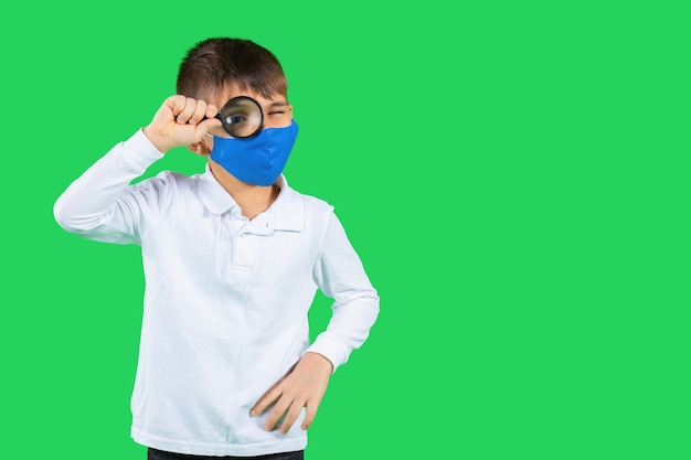 흰 셔츠와 보호 마스크를 입은 소년이 돋보기를 통해 거리를 들여다 본다.