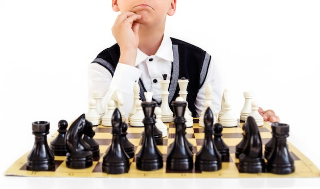 Мальчик в белой рубашке и черном жилете играет в шахматы и думает о следующем шаге