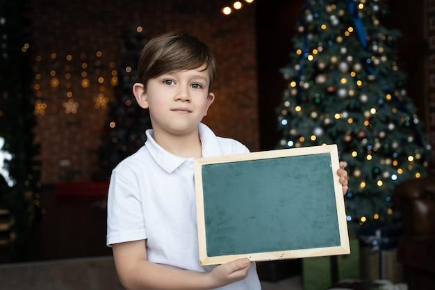 Мальчик в белой рубашке стоит у елки и держит доску с пустым местом для текста. концепция рождественских праздников