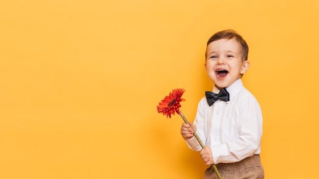 白いシャツ、ズボン、蝶ネクタイを着た男の子がガーベラの花を手に持っています。