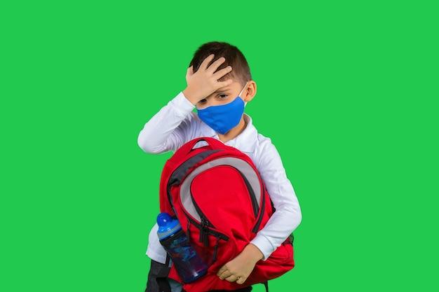学校のバックパックを手に持ち、保護マスクが疲れている白いシャツを着た少年