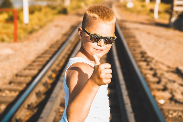 白いtシャツと黒い眼鏡をかけた男の子が鉄道に立っています。