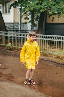 Мальчик в желтом плаще выходит под дождем. ребенок прыгает на узких участках. прыгать по грязным лужам. счастливое и беззаботное детство