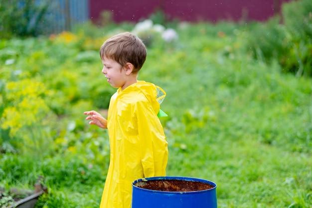 Мальчик в желтом плаще выходит под дождем. красивый и улыбающийся ребенок на улице. яркая одежда. гулять под дождем.