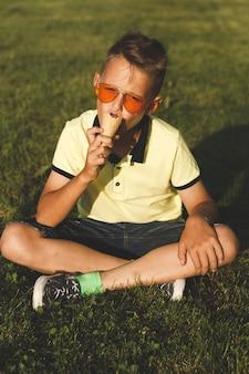 黄色いtシャツを着た男の子が草の上に座ってアイスクリームを食べます。アジアの外観