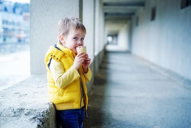黄色い卵黄の少年が長い灰色の廊下の背景でアイスクリームを食べる