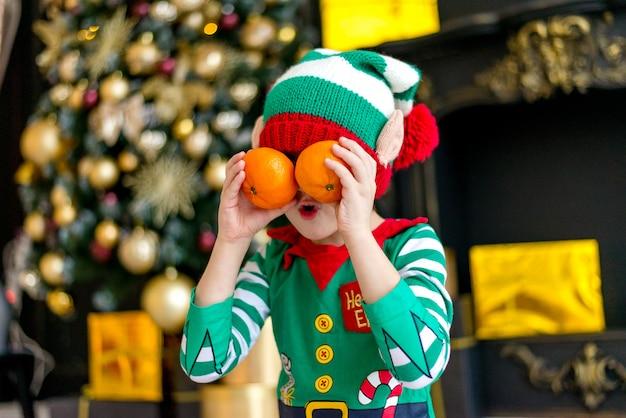 Мальчик в костюме эльфа с мандаринами у елки ждет рождества