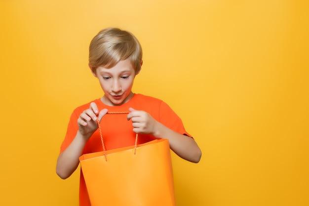 주황색 티셔츠와 노란색 배경을 가진 소년이 손에 쇼핑백을 들고 놀라서 그것을 들여다본다