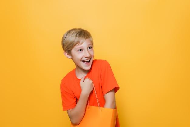 주황색 티셔츠와 노란색 배경의 소년은 종이 쇼핑백에 손을 넣고 즐겁게 웃는다
