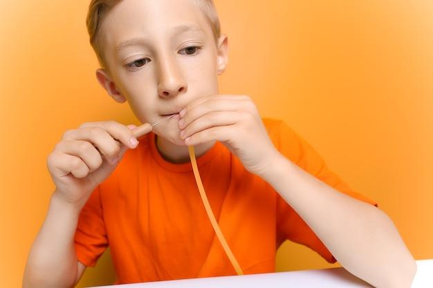 オレンジ色のtシャツを着た少年が薄い色とりどりの紙片を噛む