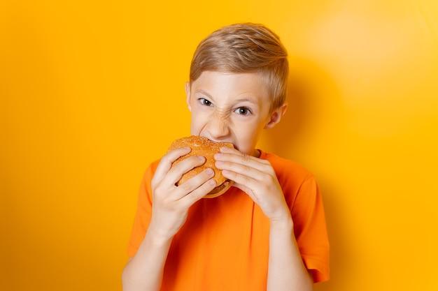 주황색 티셔츠를 입은 소년은 두 손에 햄버거를 들고 노란색 배경에 탐욕스럽게 그것을 물어뜯는다