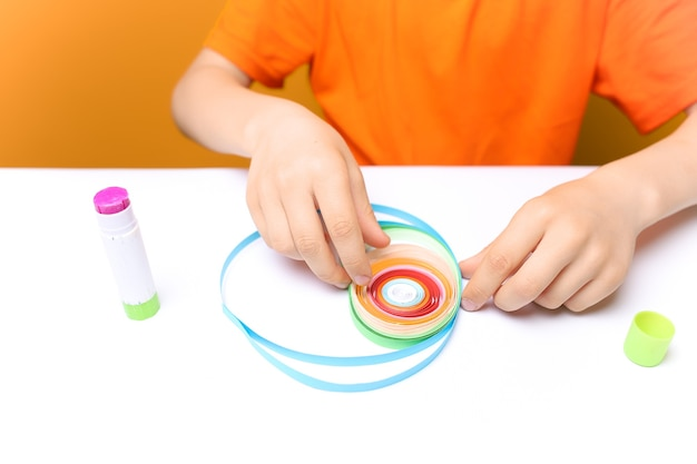 オレンジ色のtシャツを着た男の子が白いテーブルに座って、ねじれた薄い紙片を指で調整し、折り紙とクイリングの技法で工芸品を作ります。