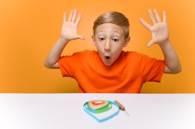 オレンジ色のtシャツを着た男の子が白いテーブルに座って、感情的に手を上げて、クイリング技法で薄い紙片を使って行われた作業を確認します。